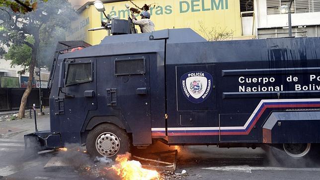 Un vehículo policial atraviesa una barricada establecida por los manifestantes de Caracas