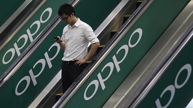 Un usuario se desplaza en unas escaleras con la publicidad de Oppo