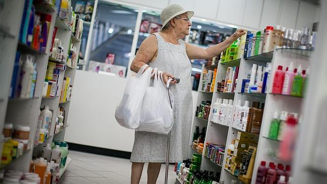 Una mujer busca medicamentos en una farmacia de Caracas