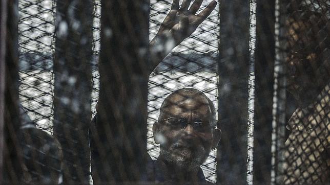 Líder de los Hermanos Musulmanes Mohamed Badie saluda tras las rejas durante uno de los juicios contra la hermandad en El Cairo