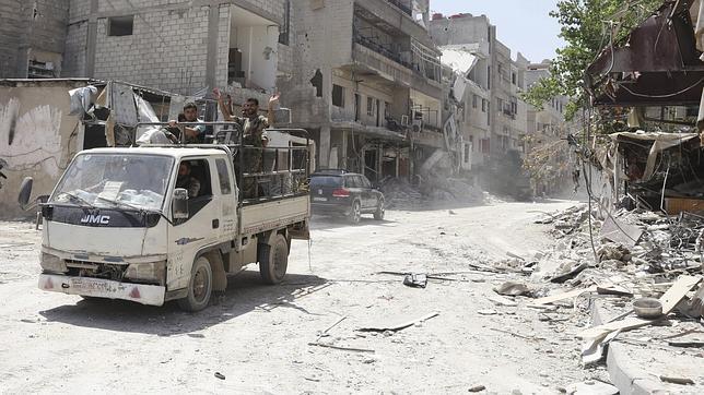 Soldados de las Fuerzas Armadas sirias patrullan por la ciudad de Mleha, al este de Damasco