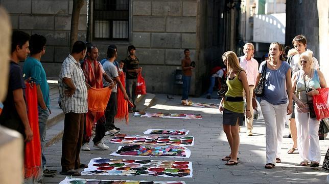 «Manteros» muestran sus productos a turistas en Barcelona