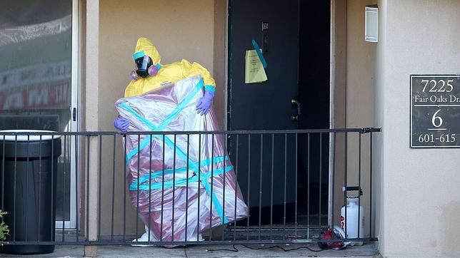 Un operario de limpieza extrae objetos del apartamento donde residió el ciudadano liberiano contagiado de ébola antes de ingresar en el hospital de Dallas