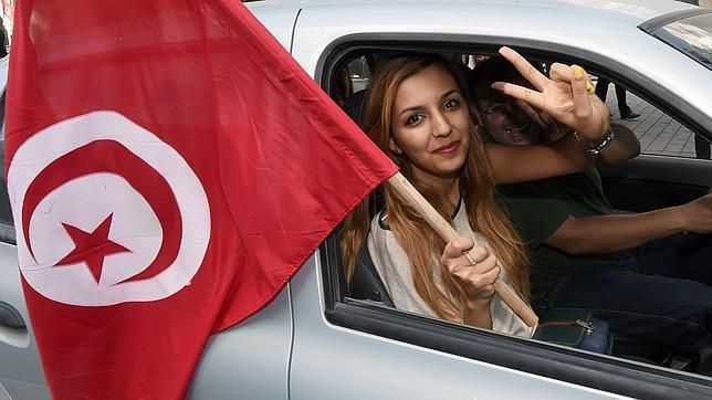 Una mujer ondea una bandera tunecina durante la jornada electoral de ayer