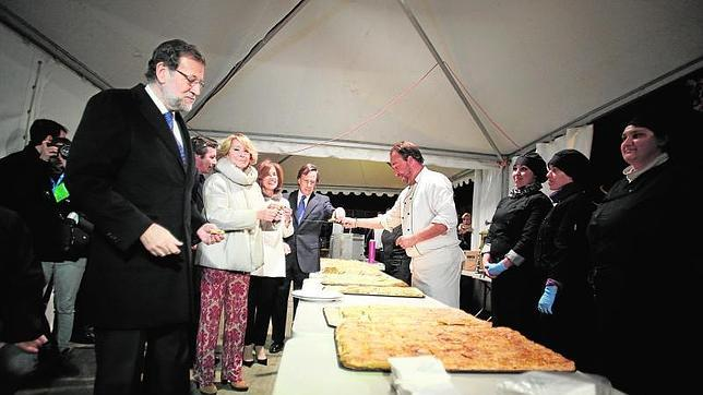 Rajoy y Aguirre, en un primer plano a la izquierda, cogiendo empanada para su cena navideña