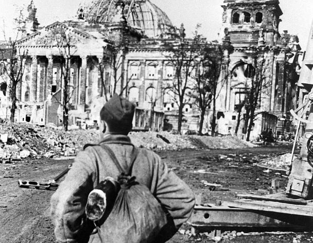 Un soldado soviético observa el edificio del Reichstag destruido