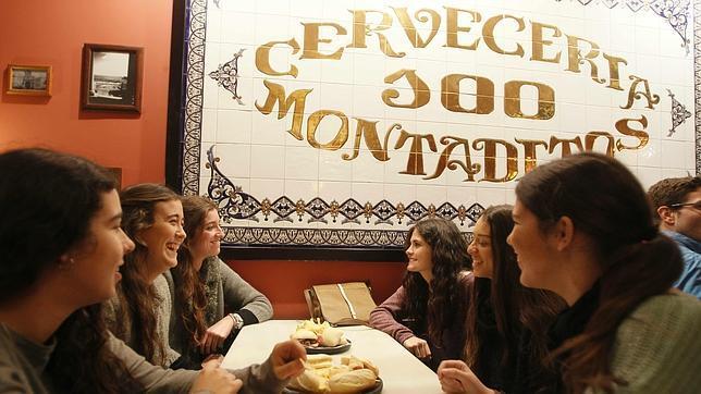 Varios jóvenes conversan en un «100 Montaditos» de Sevilla