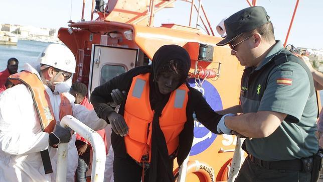 Un agente de la Guardia Civil y de Cruz Roja ayudan a una inmigrante