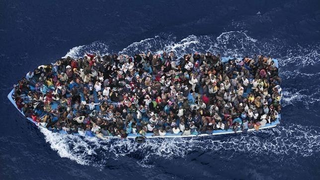 Inmigrantes en una patera, antes de ser rescatados por una fragata italiana