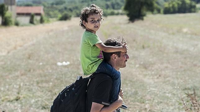 Un inmigrante camina con un niño a hombros cerca de la ciudad de Miratovac, en Serbia