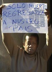 Cerca de medio millar de personas se manifestaron ayer en Valencia contra la Ley; en la imagen, un ecuatoriano despliega una pancarta en la protesta. Efe