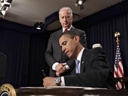 El presidente Obama firma las primeras medidas de transparencia de su Gobierno bajo la atenta mirada del vicepresidente Biden. / Afp