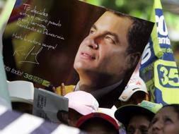 Simpatizantes del presidente ecuatoriano, Rafael Correa , del movimiento Alianza País, enseñan sus carteles electorales. / Efe