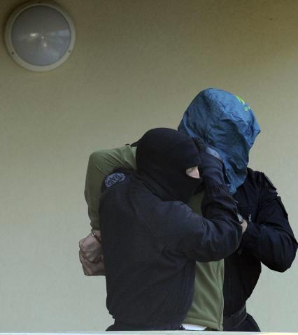 AP  Uno de los pistoleros detenidos el jueves es conducido por dos policías franceses