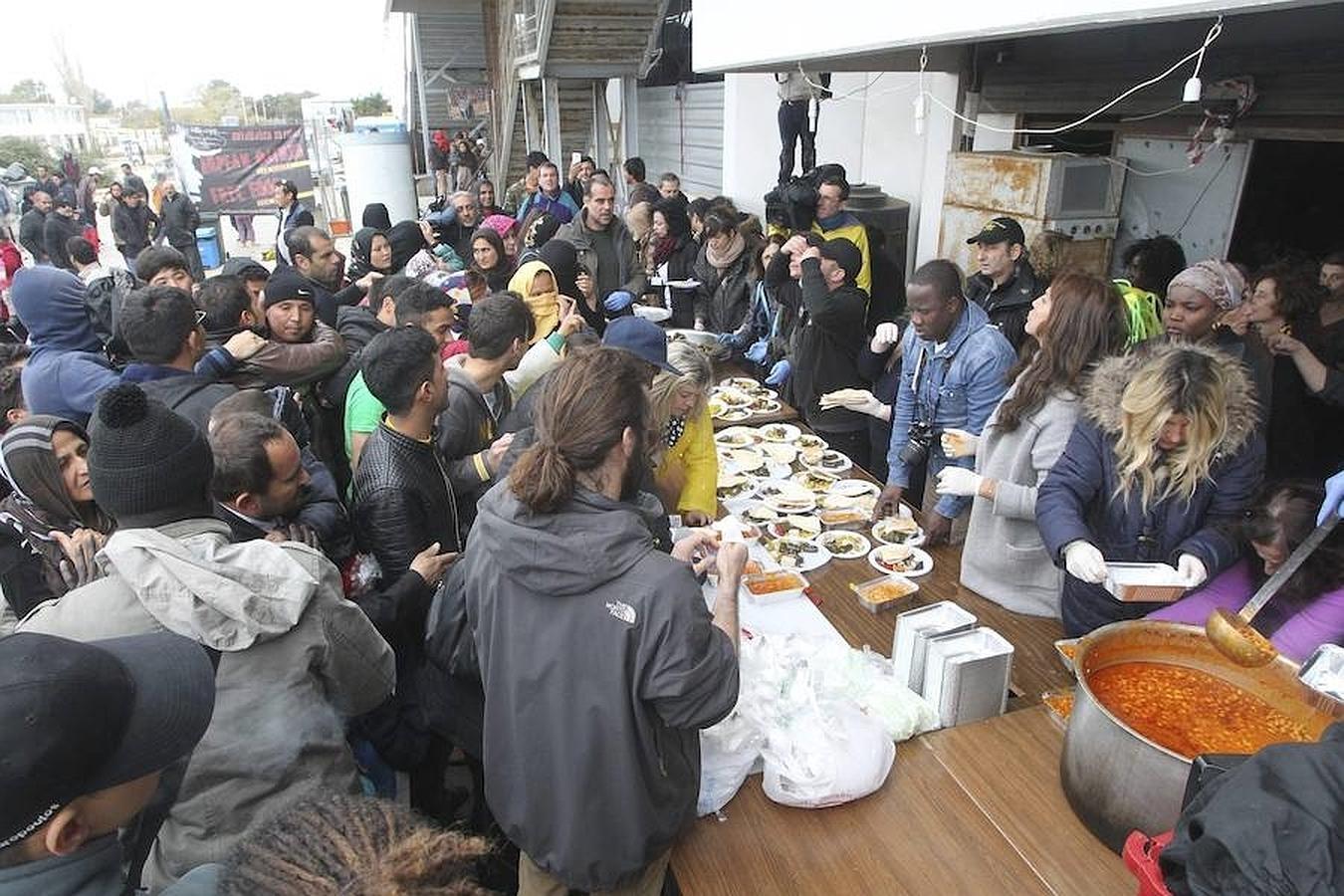 Un grupo de voluntarios reparte ayer comida a refugiados en el antiguo aeropuerto de Elliniko, Grecia
