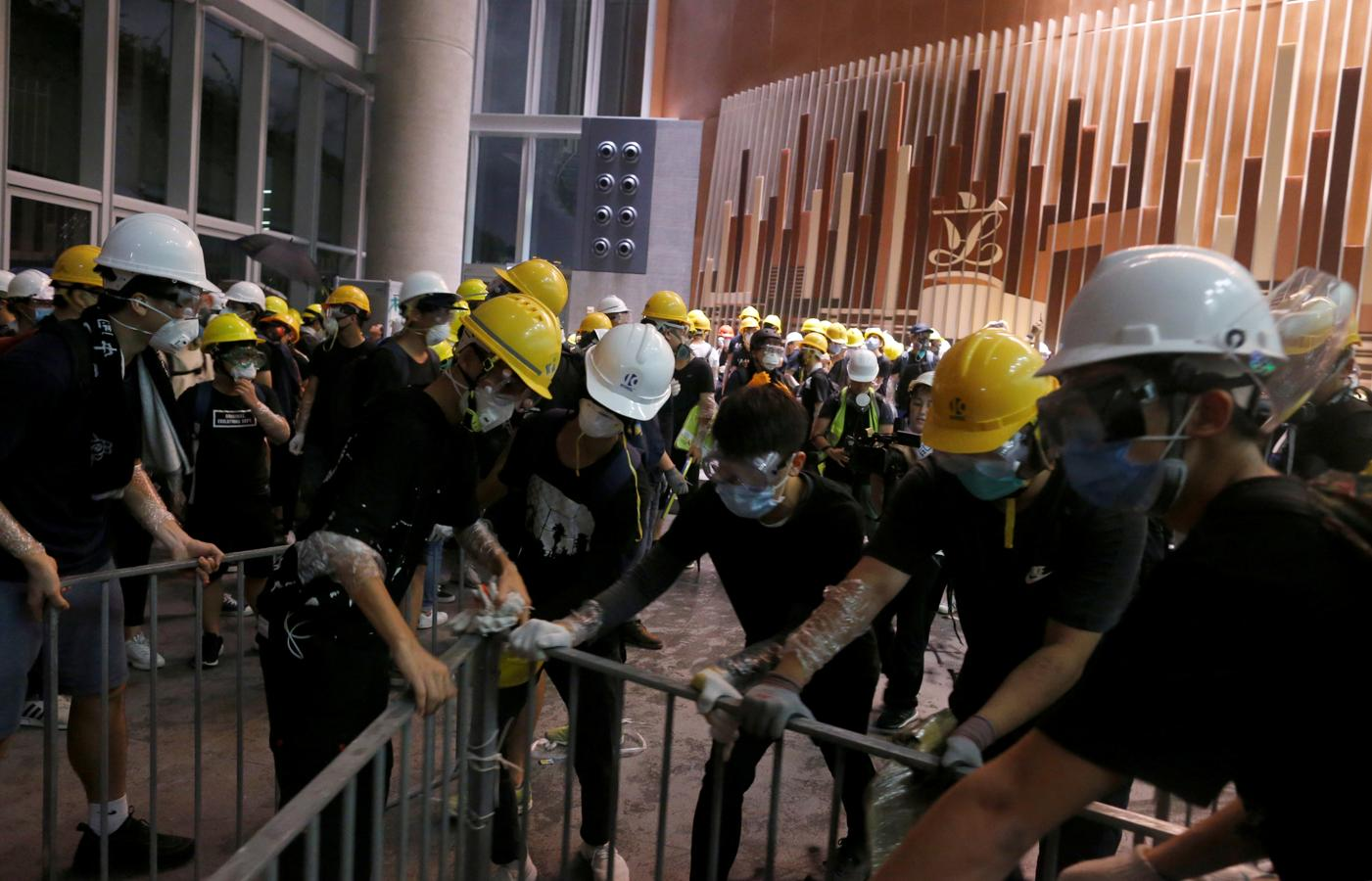 Los manifestantes utilizan barras de metal para romper las puertas y ventanas de cristal de la sede del gobierno en Hong Kong