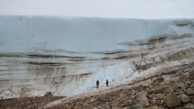 Investigadores caminan junto a una gruesa capa de hielo