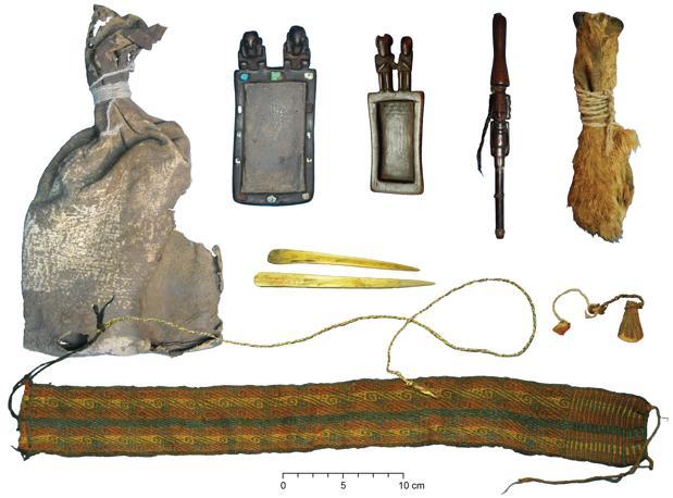 Paquete ritual con bolsa de cuero, tabletas de tabaco de madera tallada y tubo de tabaco con trenzas de cabello humano, bolsa de tres hocicos de zorro, espátulas de hueso de camélido, diadema textil de colores y cuerdas de lana y fibra