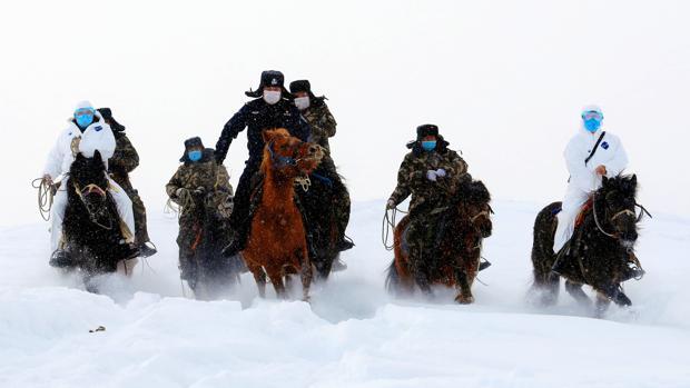 Autoridades fronterizas cabalgan a través de la nieve para informar a los residentes sobre la epidemia de coronavirus en una región montañosa de Altay, en Xinjiang, China, el pasado 19 de febrero