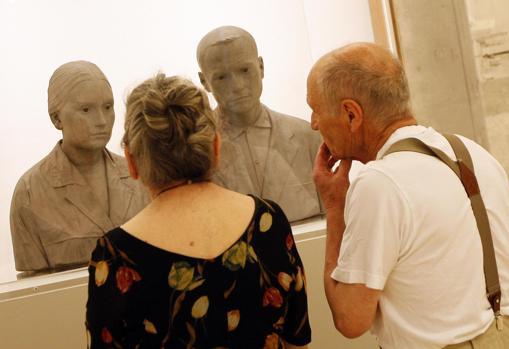 Antonio López y su esposa, María Moreno, en el Museo Thyssen junto con un retrato escultórico del matrimonio