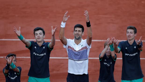 Djokovic celebra su victoria con los recogepelotas