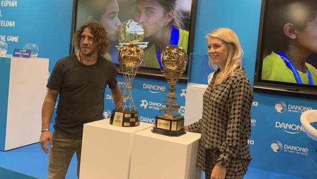 Carles Puyol y Ada Hegerberg con los trofeos de la Danone Nations Cup
