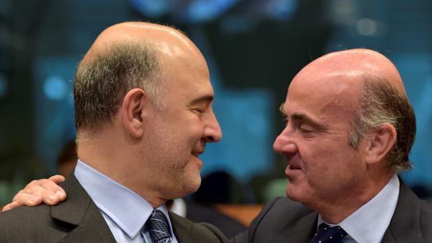 Pierre Moscovici, comisario de Asuntos Económicos, junto a Luis De Guindos en una reunión del Ecofin