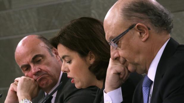 La vicepresidenta del Gobierno, Soraya Sáenz de Santamaría, acompañada por los ministros de Economía y Competitividad y de Hacienda, Luis de Guindos (i) y Cristóbal Montoro