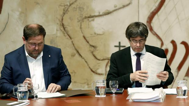 El presidente de la Generalitat, Carles Puigdemont, y su vicepresidente, Oriol Junqueras, durante la reunión semanal del gobierno catalán producida este martes