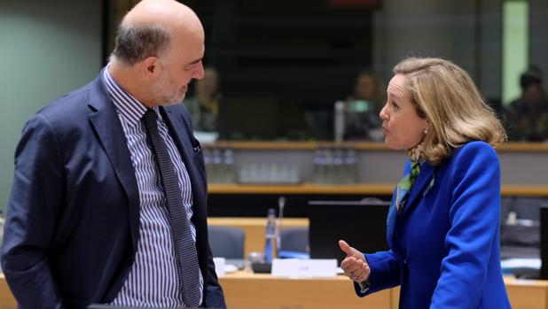 El comisario europeo de Economía y Finanzas, Pierre Moscovici (izq), conversa con la ministra de Economía española, Nadia Calviño, a su llegada a la reunión de ministros de Economía y Finanzas de la UE el pasado mes de marzo