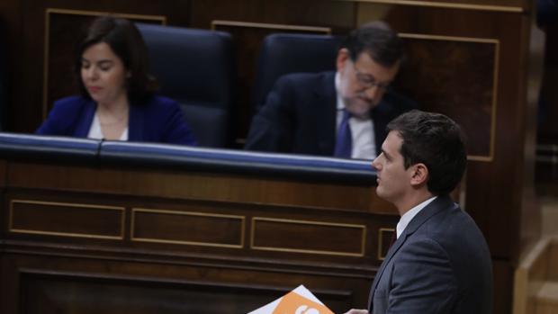 Rivera pasa junto a los escaños de Soraya Saénz de Santamería y Mariano Rajoy