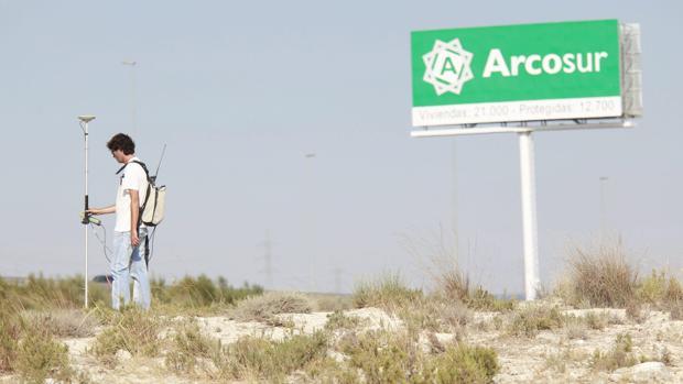 Un topógrafo, trabajando a pie de campo en terrenos de Arcosur, la gran zona de expansión urbana desarrollada en el último decenio en Zaragoza capital