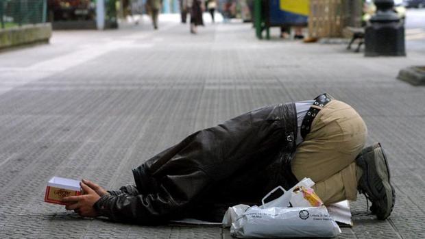 Un mendigo pide limosna en la calle