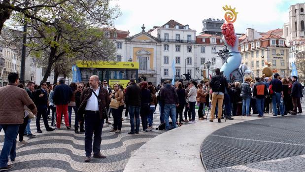 Público visitando la hoguera alicantina y la oficina de información turística en Lisboa