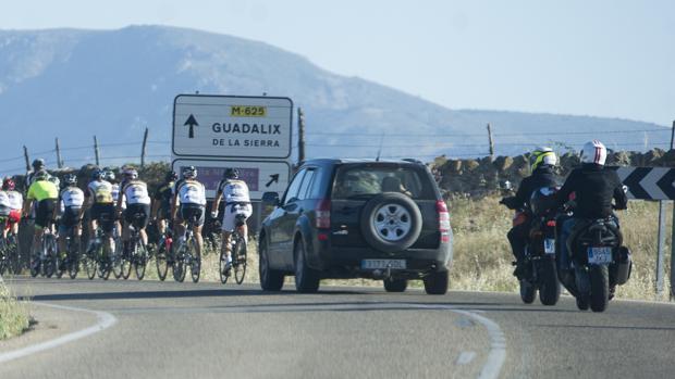 Un grupo de ciclistas circula por Guadalix de la Sierra, seguido de varios vehículos
