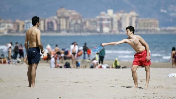 Dos jóvenes juegan a las palas en una playa valenciana