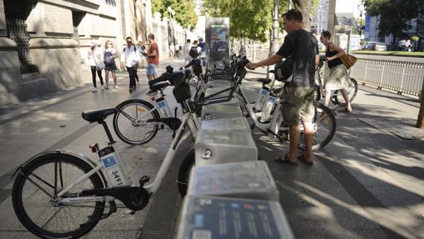 Un usuario coge una bicicleta de Bicimad en la estación de la calle Alcalá ubicada junto al Metro Sevilla