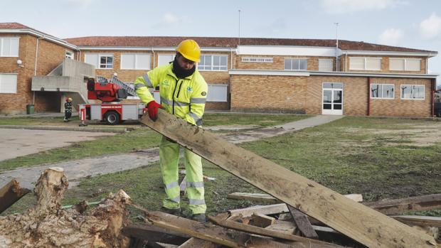 Un operario retira las maderas desvencijadas del paseo de A Lanzada, en Pontevedra
