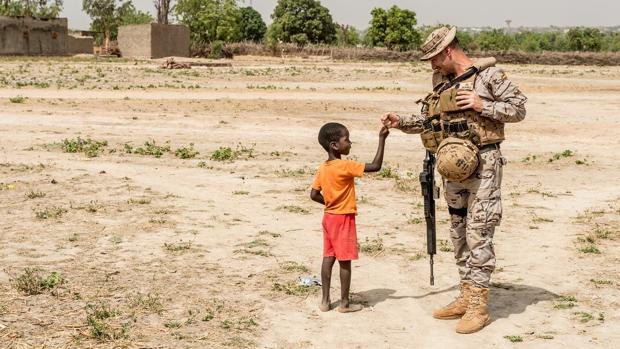 Uno de los soldados españoles con un niño, sobre el terreno maliense