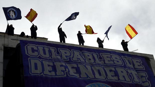 Varios okupas de Hogar Social ondean banderas en la azotea de la sede del Banco Madrid