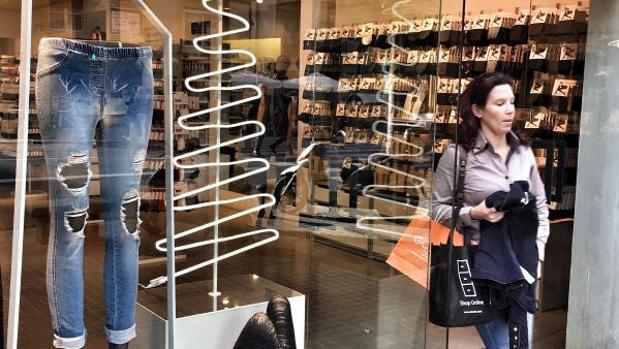 Una consumidora pasa junto a un escaparate al salir de una tienda de ropa en Valencia