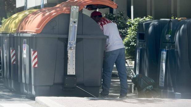 Un hombre rebusca entre la basura en Orcasitas, ayer