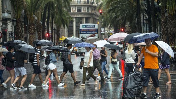Imagen de peatones que se protegen con paraguas en la plaza del Ayuntamiento de Valencia.