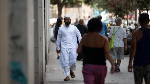 Un inmigrante pasea por las calles de la Raval