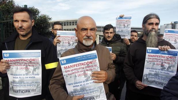 Trabajadores de Alcoa muestran las pancartas anunciando la manifestación del sábado