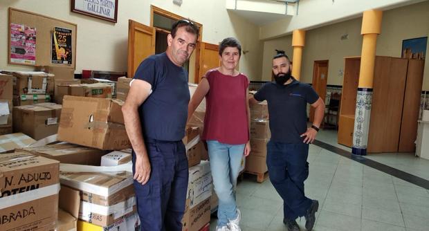 La bibliotecaria, María José Olivares, con dos voluntarios, posa ante decenas de cajas con libros donados