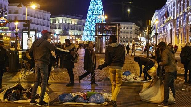 Un grupo de manteros, de noche, vende sus productos en la Puerta del Sol