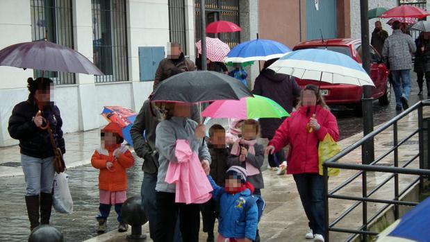 Un grupo de niños con sus madres a la salida de una escuela