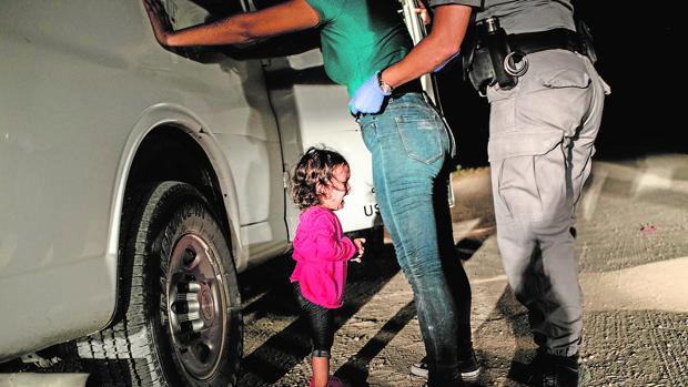 La niña Yanelaa, de Honduras, llora mientras su madre es cacheada por un policía de fronteras