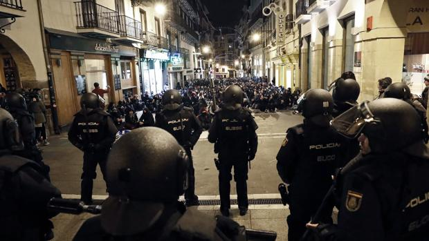 Un grupo de antidisturbios de la Policía frente a una multitud de jóvenes partidarios de la okupación